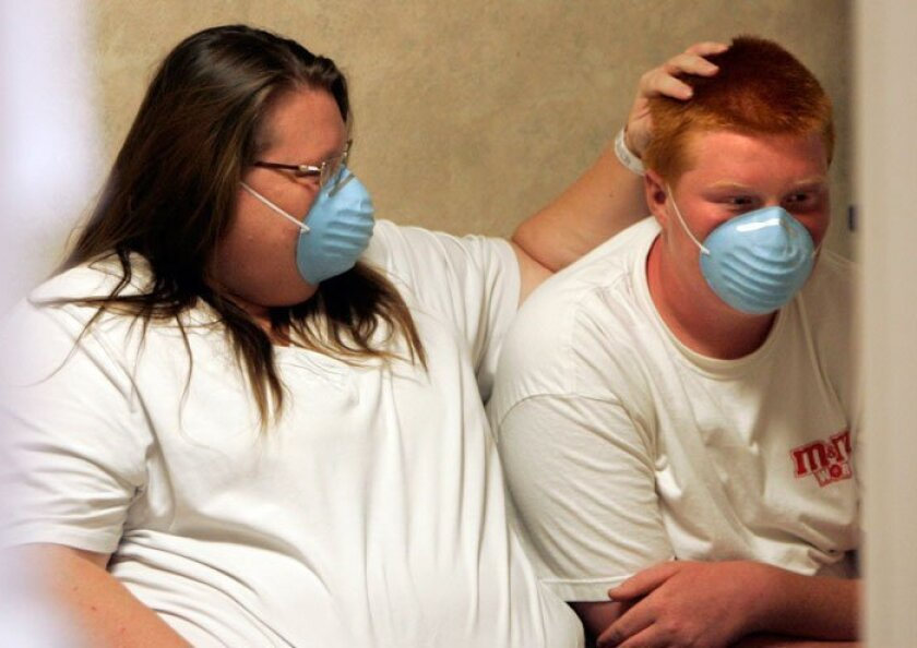 Bonni Briggs of Escondido holds the head of son Devon Raines in a hallway of the emergency room at Palomar Hospital on Wednesday, July 29.  Both came in with flu-like symptoms.
