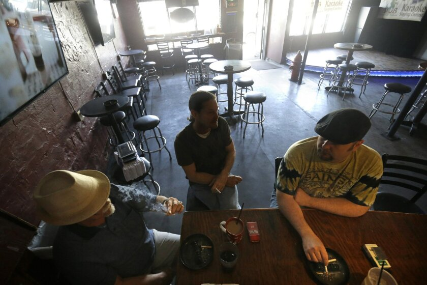 Patrons smoke inside Kajun's Pub, Tuesday, April 21, 2015, in New Orleans. Starting at midnight Tuesday, smoking will no longer be permitted in bars, gambling halls and many other public places such as hotels, workplaces, private clubs and stores. (AP Photo/Gerald Herbert)