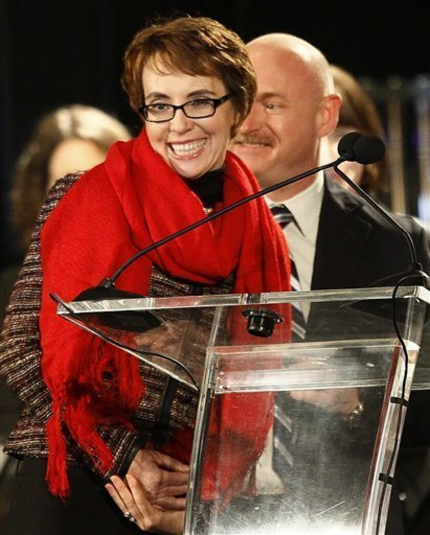 Rep. Gabrielle Giffords, left, accompanied by her husband, former astronaut Mark Kelly, reacts after leading the Pledge of Allegiance at the start of a memorial vigil remembering the victims and survivors one year after the Arizona congresswoman was wounded in a shooting that killed six others, Sunday, Jan. 8, 2012, in Tucson, Ariz. (AP Photo/Ross D. Franklin)