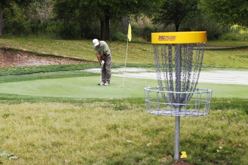 Golfer James Jones putts at Reidy Creek Golf Course in Escondido. In the foreground is one of the new Disc Golf baskets installed at the course. Officials at the course are preparing for a Saturday opening of the disc course, which they hope will increase revenues at the struggling business.