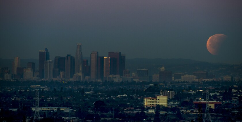 A Super Blue Blood Moon sets over downtown Los Angeles skyline in 2018, as viewed from Whittier.