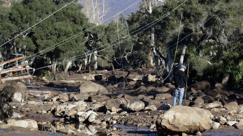 A man stands near downed power lines in Montecito on Jan. 10.
