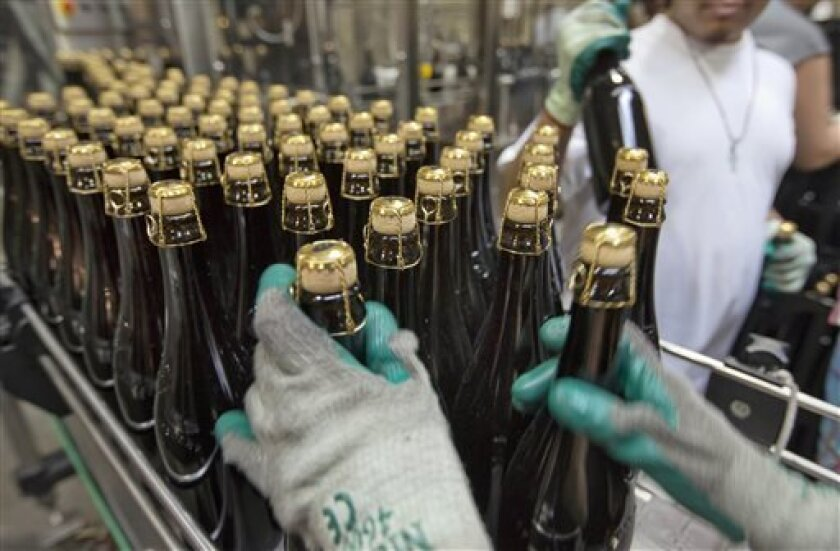 FILE - In this July 1, 2013, file photo, bottles of Brooklyn Local 2 are loaded on to a conveyor for labeling, at the Brooklyn Brewery, in the Williamsburg section of the Brooklyn borough of New York. The Commerce Department reports on orders placed with U.S. factories in July on Thursday, Sept. 5, 2013. (AP Photo/Richard Drew, File)