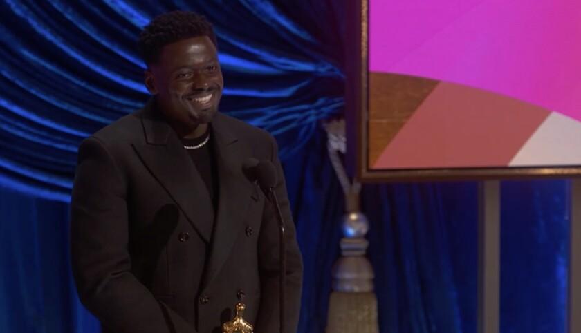 Daniel Kaluuya smiles and holds his Oscar
