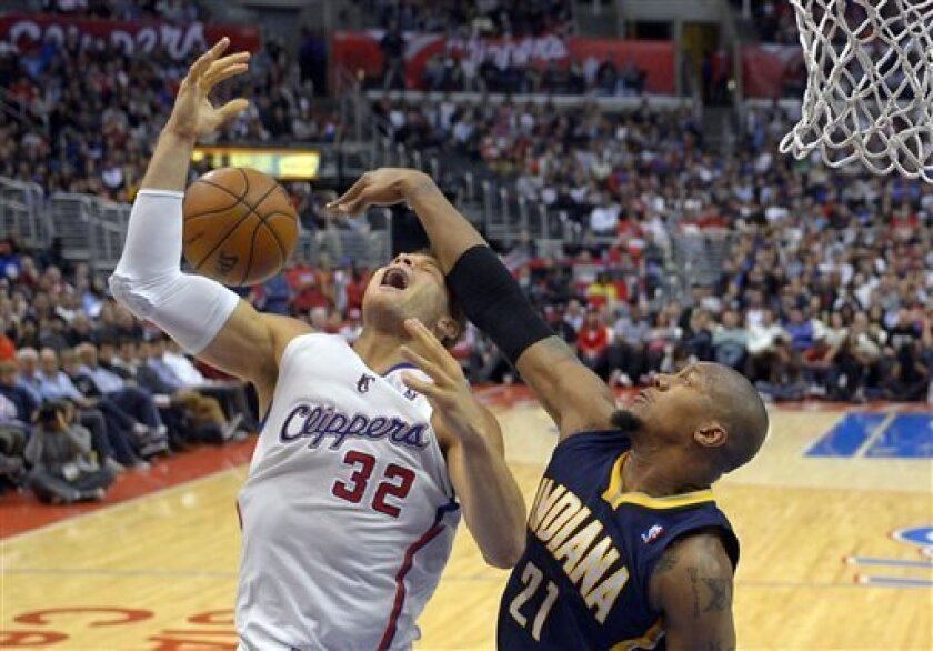 Los Angeles Clippers forward Blake Griffin, left, has his shot rejected by Indiana Pacers forward David West during the first half of their NBA basketball game, Monday, April 1, 2013, in Los Angeles. (AP Photo/Mark J. Terrill)