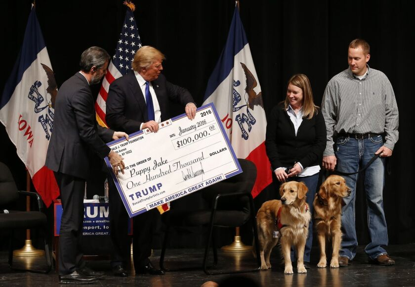 Presidential candidate Donald Trump presents an enlarged copy of a $100,000 contribution from the Donald J. Trump Foundation to Puppy Jake, a veterans charity, at a 2016 campaign event in Davenport, Iowa.