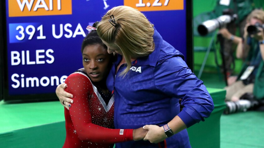 American gymnast Simone Biles is embraced by her coach, Aimee Boorman, after a disappointing performance on the balance beam during the individual finals on Monday.