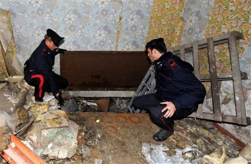 Italian Carabinieri paramilitary police officers look at a passage in a room reportedly used by top mafia fugitive Giuseppe Setola, to elude capture and escape from his hideout into the sewer in Caserta, southern Italy, Monday Jan. 12, 2009. Carabinieri Col. Domenico Forte said police were closing