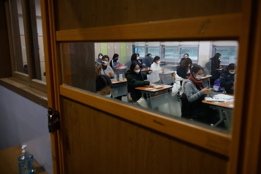 Students wearing face masks wait for the start of college entrance examination at an exam hall in Seoul.