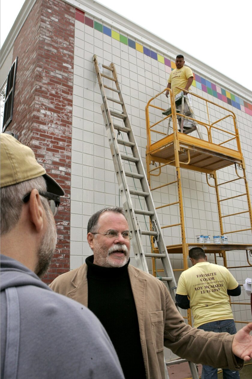Artist Roy McMakin talks with people while standing near the wall of a commercial building (behind him) with 870 seven-inch-square bricks that are being painted individually from a choice of 60 different colors. Above on the scaffolding is one of the project's painters Guillermo Arellano. CHARLIE N