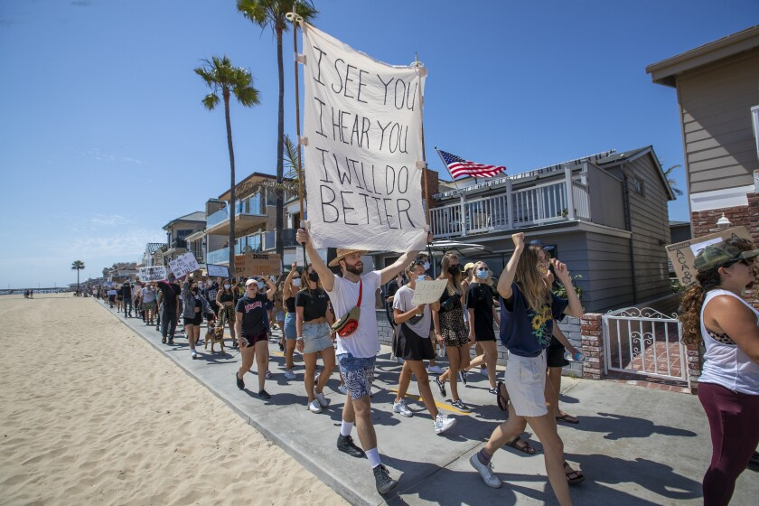 """Protesters march down a beachfront bike path in Newport Beach. A sign reads """"I see you. I hear you. I will do better."""""""
