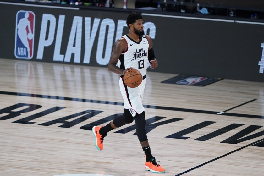 Clippers forward Paul George brings the ball up court against the Mavericks during Game 5 on Tuesday.