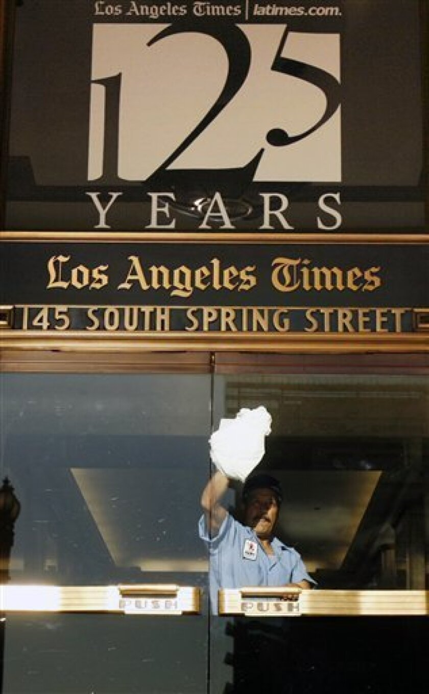 """FILE - In this Nov. 16, 2006 file photo, a worker cleans an entrance to the Los Angeles Times building in Los Angeles. Federal authorities allege that Matthew Keys provided hackers with login information to access the Tribune Company's computer system in December 2010. Keys had been fired months before from a Sacramento television station owned by Tribune. Keys was a web producer for KTXL. Tribune also owns the Times. The investigators allege that Keys gave a hacker named """"Sharpie"""" the informa"""