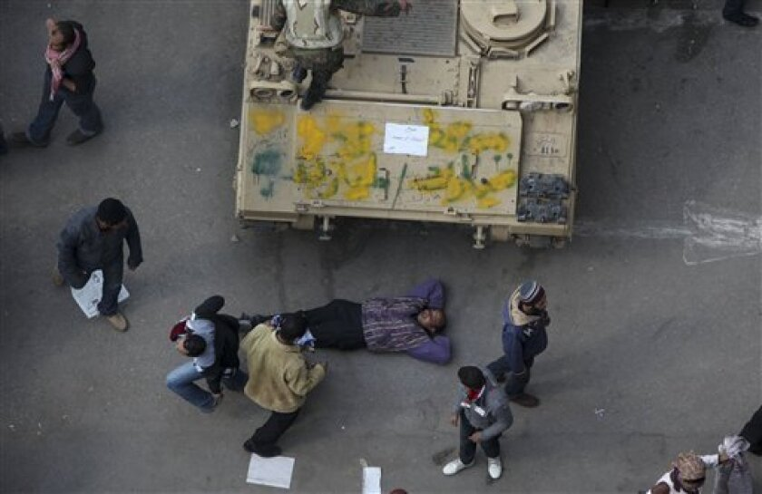 An anti-government protester lies down near an Egyptian army vehicle after traditional Muslim Friday prayers at the continuing demonstration in Tahrir Square in downtown Cairo, Egypt Friday, Feb. 11, 2011. (AP Photo/Tara Todras-Whitehill)