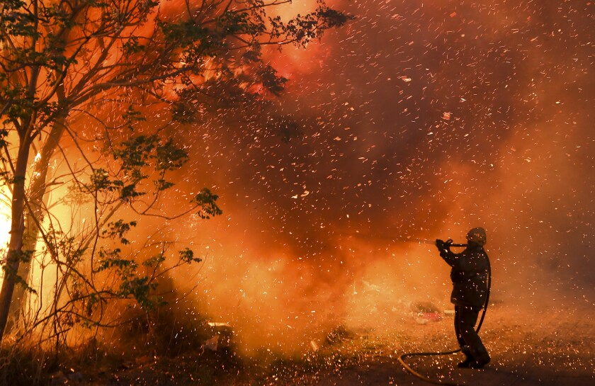 A firefighter battles flames in Cordoba, Argentina, Monday, Oct. 12, 2020. Wildfires have destroyed thousands of hectares in the Argentine province of Cordoba this year, amid a drought and high temperatures. (AP Photo/Nicolas Aguilera)