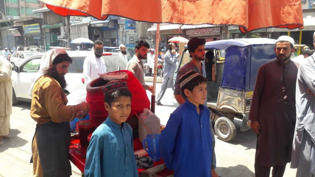 Umar Gul, left, and his cousin Muhammad Siraj work at a lemonade cart in Peshawar, Pakistan.