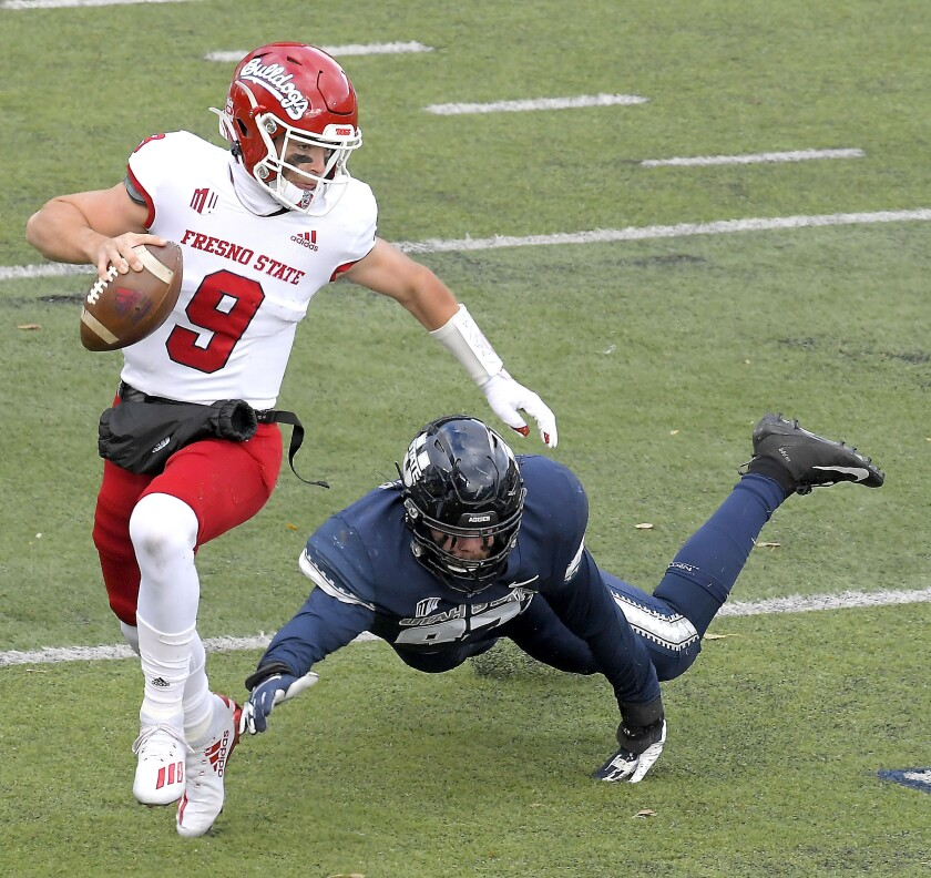 Fresno State quarterback Jake Haener (9) scrambles away from Utah State defensive lineman Jake Pitcher (97) during the first half of an NCAA college football game, Saturday, Nov. 14, 2020, in Logan, Utah. (Eli Lucero/Herald Journal via AP)