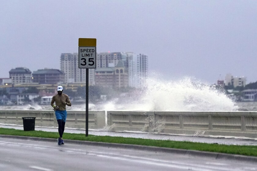 A jogger along the Tampa shoreline as a wave breaks over a seawall