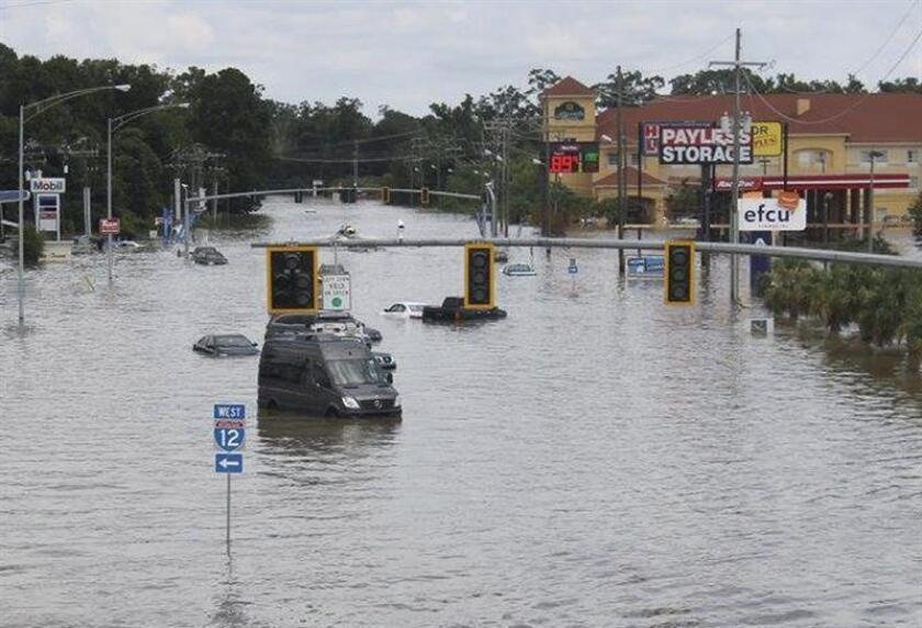 """Fotografía facilitada por el Departamento de Transporte y Desarrollo de Luisiana (DOTD), muestra vehículos prácticamente cubiertos por el agua que inunda las calles de Baton Rouge en Luisiana (Estados Unidos) ayer, 14 de agosto de 2016. Las inundaciones """"sin precedentes"""" registradas desde el viernes en Luisiana, en el sur de EE.UU., han dejado tres muertos y han obligado a rescatar a unas 7.000 personas de sus hogares y vehículos, informaron hoy las autoridades locales. EFE/Louisiana"""