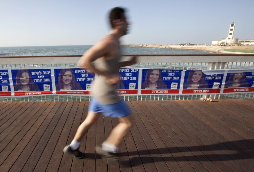 A jogger passes a line of posters supporting Shelly Yachimovich, leader of the Israeli Labor Party, in Tel Aviv on Tuesday.