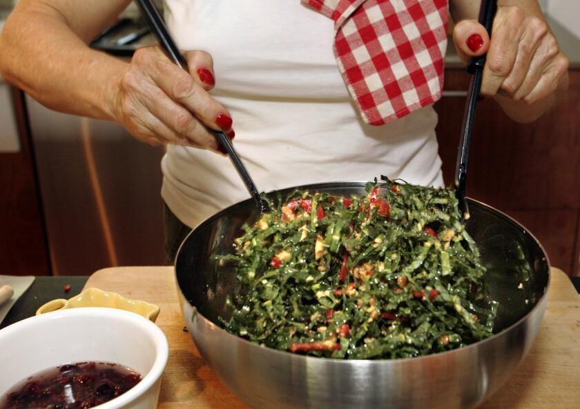 A woman tosses a salad