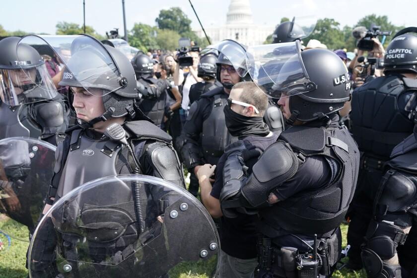 Varios policías rodean a un hombre (al centro, con anteojos) durante un mitin cerca del Capitolio de Estados Unidos