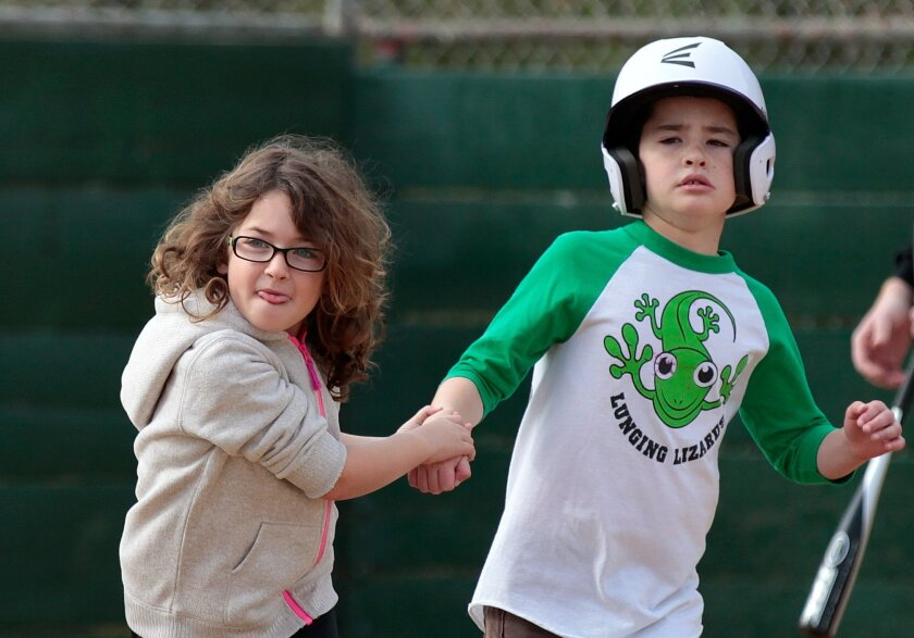 Paul Rosenberg, 9, of the Lunging Lizards is escorted to first base by his younger sister Brooke Rosenberg during an  adapted baseball game for youth with autism in Rancho Penasquitos Saturday.