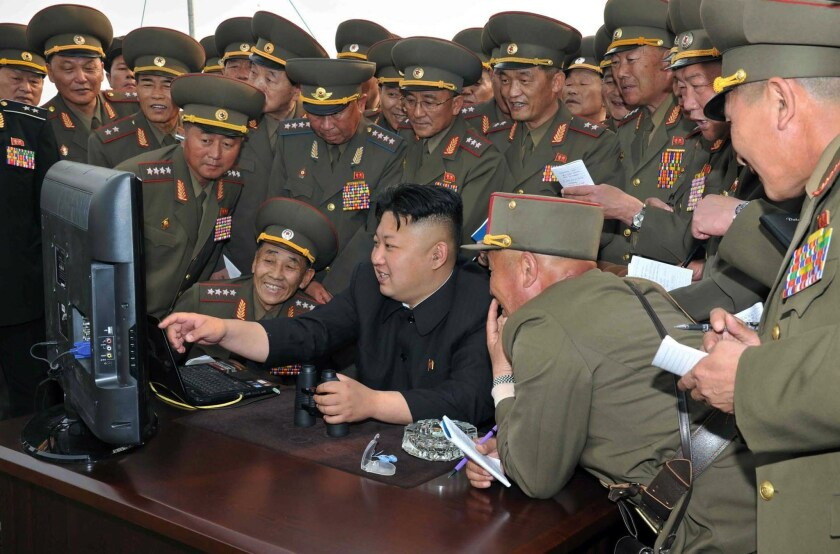 North Korean leader Kim Jong Un, center, is shown at a defense facility computer in this photo released in April. Only the political elite and high-ranking military have access to the Internet in North Korea.