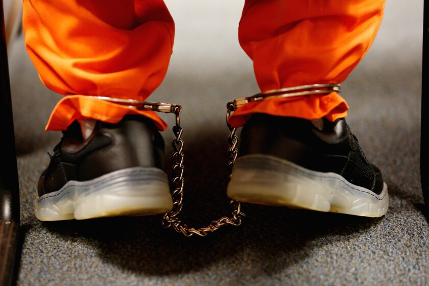 Close-up of metal cuffs around the ankles of a juvenile respondent in court
