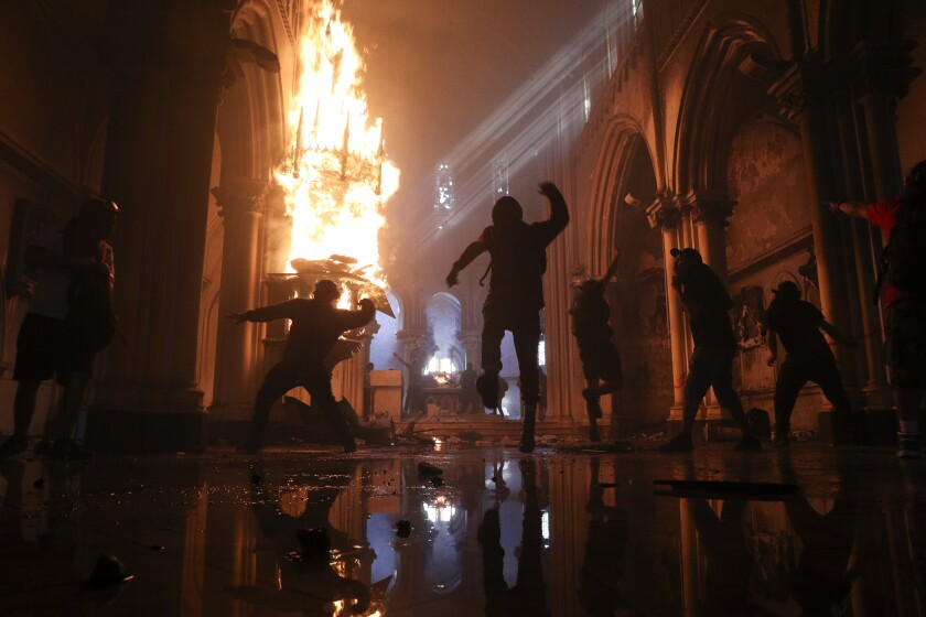The statue of a saint is engulfed as the San Francisco de Borja church in Santiago, Chile, burns on Oct. 18.