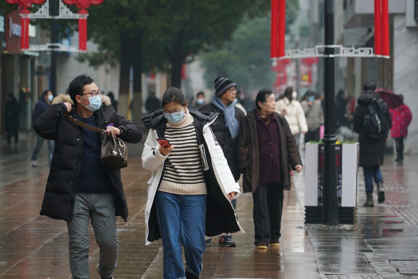 Masked pedestrians walk down a shopping street in downtown Wuhan, China. The new coronavirus outbreak, as of Jan. 31, had resulted in at least 213 people dead and more than 9,709 cases confirmed in mainland China, as the virus spreads globally.