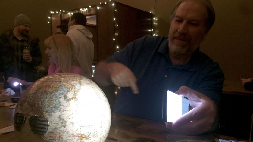 Bob Knodel, host of Globebusters channel on YouTube, who believes Earth is flat, tries to prove it with a globe at a flat Earth meeting in Golden, Colo.
