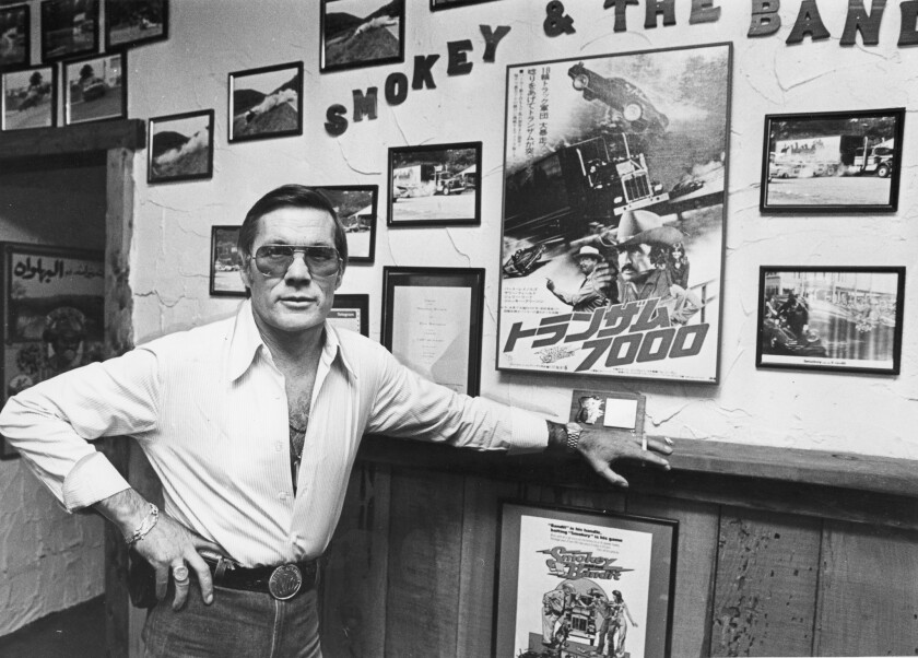 """Hal Needham in 1980 with photos and posters from the movie """"Smokey and the Bandit,"""" which he directed."""