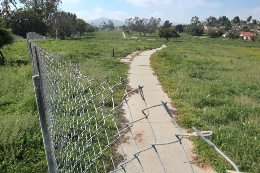 View looking west from La Brea Street of a part of the fenced off Escondido Country Club.