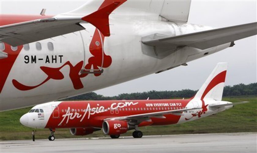 FILE - In this Dec. 9, 2010 file photo, AirAsia aircrafts sit at Kuala Lumpur International Airport's low cost carrier terminal in Sepang, Malaysia. Three Asian flag carriers have announced plans to set up new low-cost airlines, jumping on the budget airline bandwagon as their cheap and cheerful rivals grab an ever bigger share of passengers and make inroads into the long-haul business. (AP Photo/Lai Seng Sin, File)