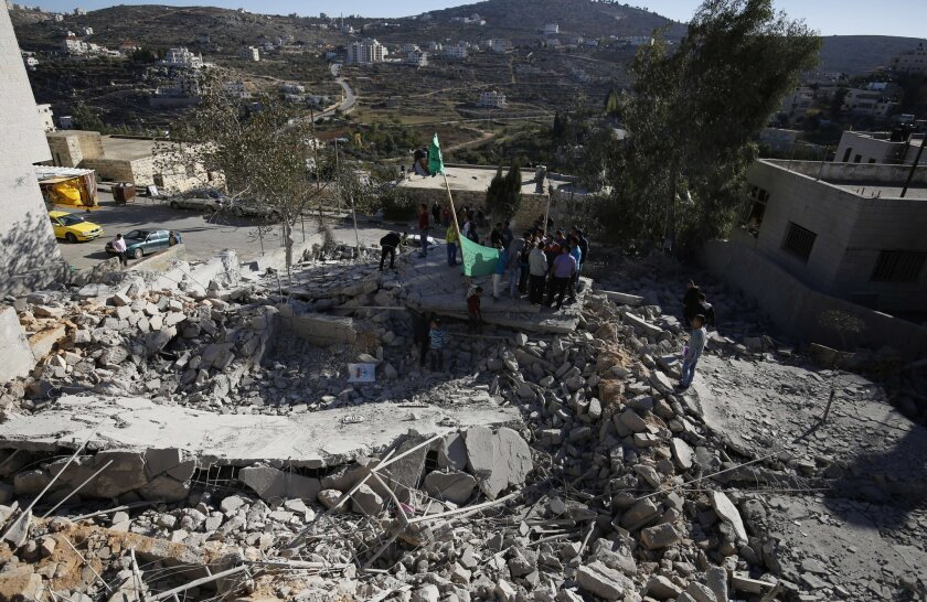 Palestinians look at rubble of the house of a Palestinian man who the Israeli military said killed an Israeli traveling to the West Bank in June. The home in Silwad was demolished Nov. 14 by the Israeli army.
