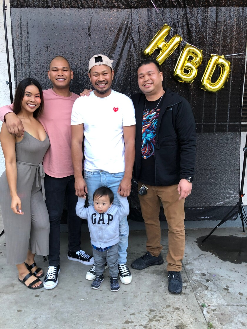 Rickie Chhoeun, in white T-shirt, poses at a birthday party with two brothers and his sister at her Long Beach home in June 2019.