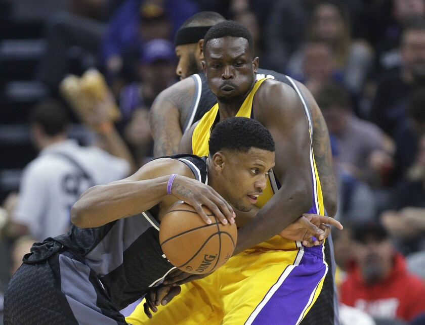 Kings forward Rudy Gay, left, tries to drive past Lakers forward Luol Deng during the first quarter.