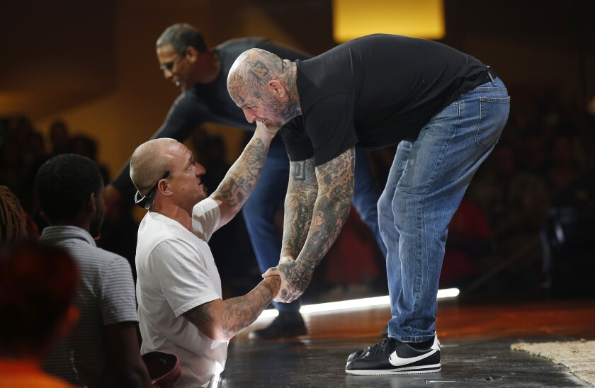 """Jeff """"Taz"""" Tanzella, a former white supremacist, right, shakes the hand of Andy Yates of Escondido during a service at the Rock Church in Point Loma on August 25, 2019. Pastor Miles McPherson, in back, invited Tanzella to share his story with the racially-diverse congregation."""