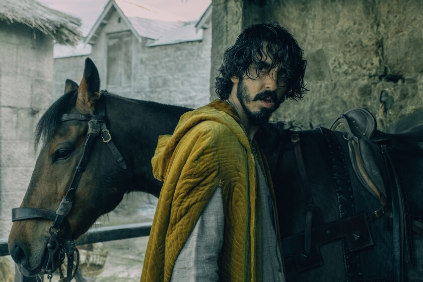 """Dev Patel stands next to a horse in the movie """"The Green Knight."""""""