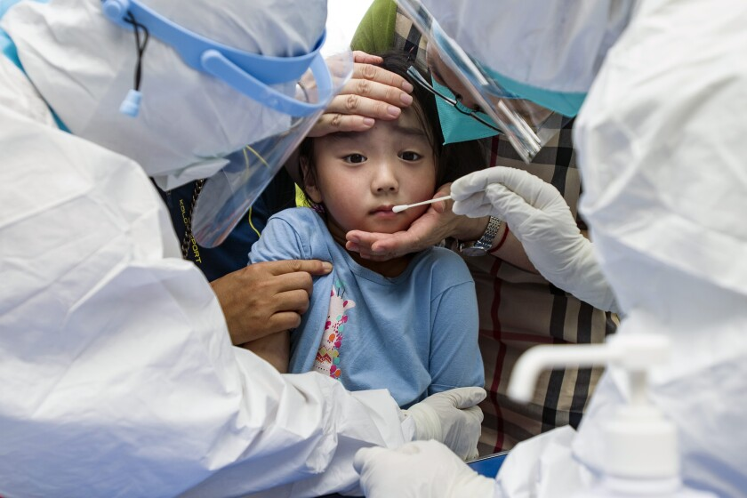 A child reacts to a throat swab during mass testing for COVID-19 in Wuhan in central China's Hubei province Tuesday, Aug. 3, 2021. The coronavirus's delta variant is challenging China's costly strategy of isolating cities, prompting warnings that Chinese leaders who were confident they could keep the virus out of the country need a less disruptive approach. (Chinatopix via AP)