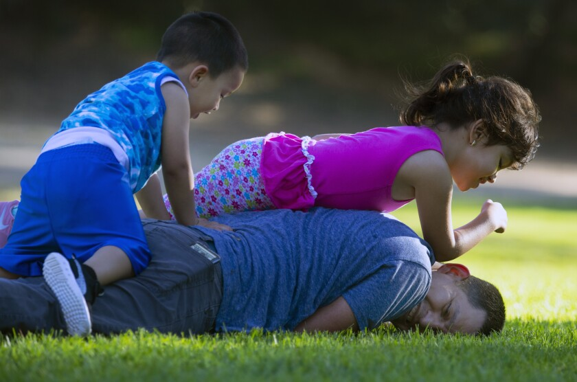A man plays with his young children in Griffith Park on Father's Day
