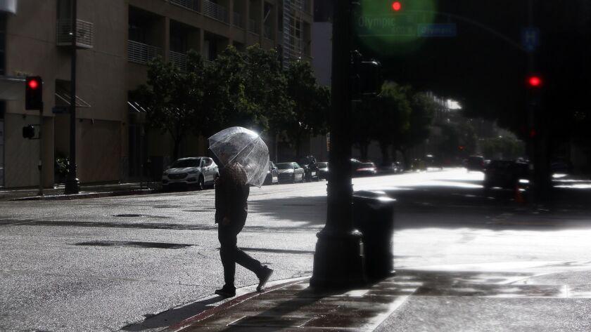 LOS ANGELES, CA-FEBRUARY 4, 2019: Cesar Leyva crosses the street downtown on a rainy day on February