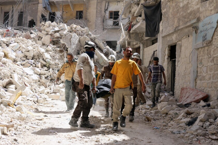 Syrian Civil Defense workers evacuate a body after a government airstrike on Tuesday in the northern city of Aleppo.