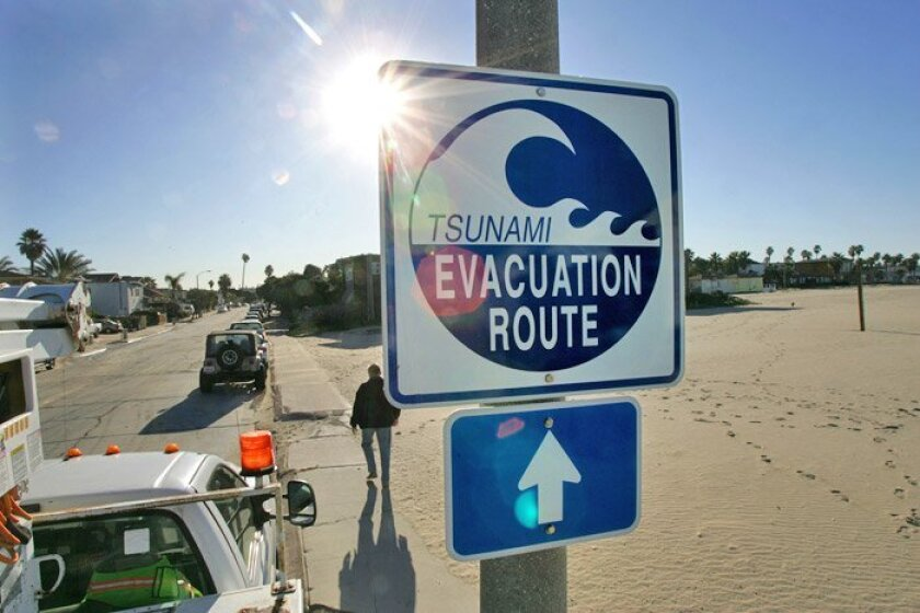 A Tsunami Evacuation Route sign at the corner of Spray Street and Brighton Avenue in Ocean Beach shows what direction to take away from the beach.
