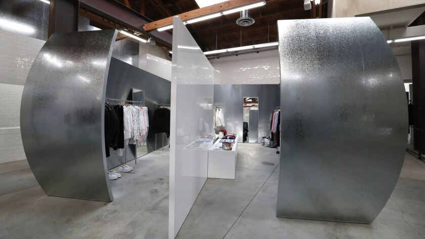 Curved galvanized metal walls frame the Comme des Garçons Homme Plus and Shirt space inside the new Dover Street Market Los Angeles.