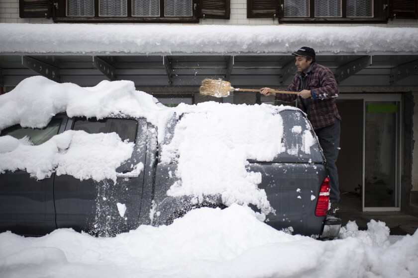 A man cleares his car of snow, on Monday, Dec. 7, 2020, in Valens, Switzerland. Large amounts of snow fell in parts of Switzerland over the weekend. (Gian Ehrenzeller/Keystone via AP)