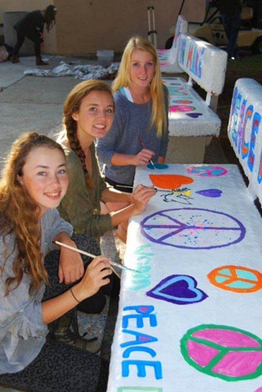Madeleine Garay, Summer Broekema and Sophia Bourne paint a bench with peaceful messages for World Peace Day, Sept. 21.