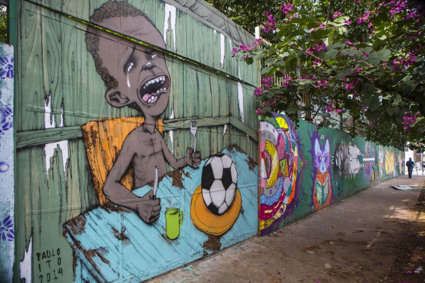 Graffiti of a crying child who is served a soccer ball to appease his hunger covers a portion of a public school wall in Sao Paulo.