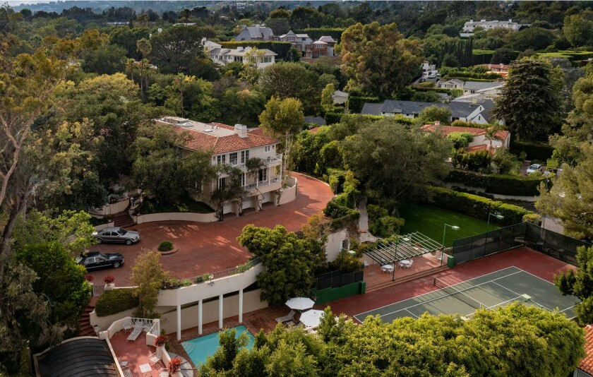 An aerial view shows a mansion, a large sports field, a swimming pool and a tennis court.